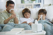 Sick father and sons blowing noses and checking temperature on living room sofa