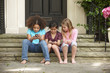 Girls text messaging with cell phones on front stoop