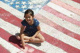 Smiling Chinese girl with chalk coloring American flag on sidewalk
