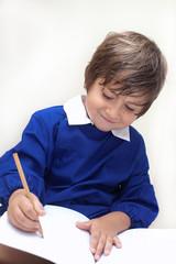 bambino con grembiule scrive nel quaderno