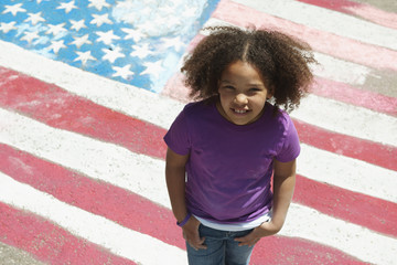 Smiling mixed race girl standing in front of chalk colored American flag