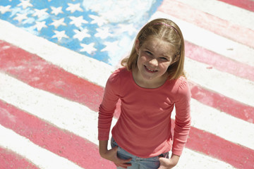 Smiling Caucasian girl standing in front of chalk colored American flag