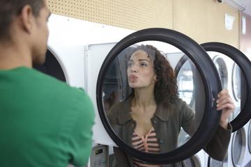 Mixed race woman kissing dryer door