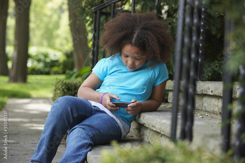 Mixed race girl text messaging with cell phone on front stoop