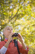 Caucasian woman using binoculars outdoors