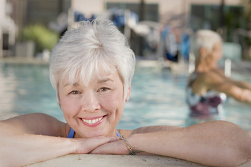 Mixed race woman leaning on edge of swimming pool