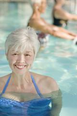 Mixed race woman enjoying swimming pool