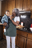 Black grandmother feeding grandson in kitchen