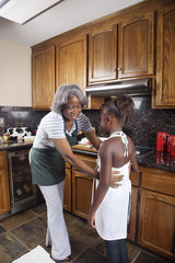 Black grandmother cooking with granddaughter