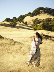 Caucasian woman standing in field wrapped in blanket