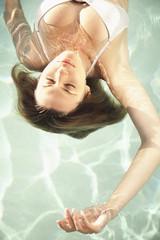 Caucasian woman floating in swimming pool