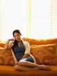 Asian woman reclining on sofa