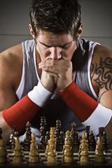 Body builder playing chess