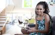 Mixed race girl using digital tablet in living room