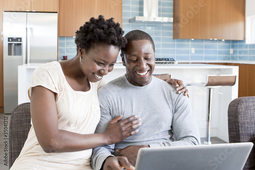Black couple hugging and using laptop