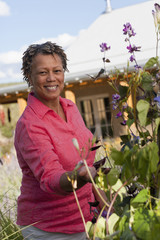 Black woman looking at flowers in garden