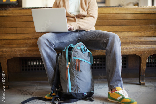 Caucasian man sitting on bench using laptop