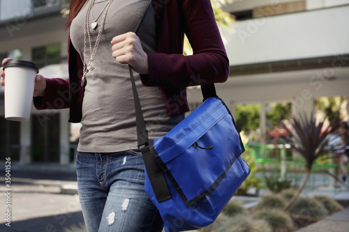 Caucasian woman walking with messenger bag and coffee
