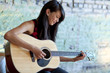 Asian girl strumming guitar