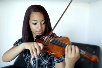 Mixed race girl practicing violin