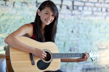 Asian girl strumming guitar