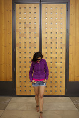 Hispanic woman standing near wooden door