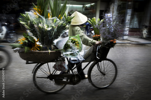 Vietnamese person carrying flowers on bicycle