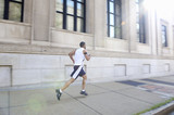 African American man running on city sidewalk