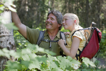 Caucasian father and daughter hiking in forest