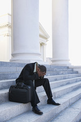 Frustrated African American businessman sitting on courthouse steps