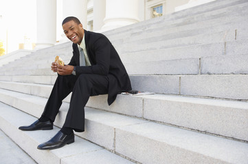 African American businessman eating sandwich on courthouse steps