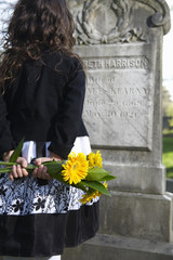 Hispanic girl with flowers visiting cemetery
