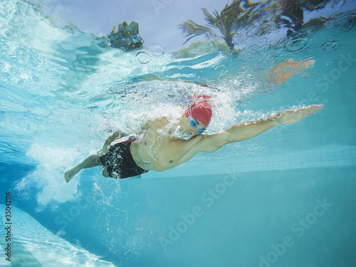 Mixed race man swimming in swimming pool