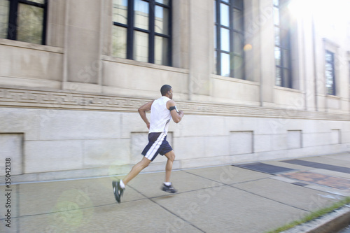 African American man running on city sidewalk