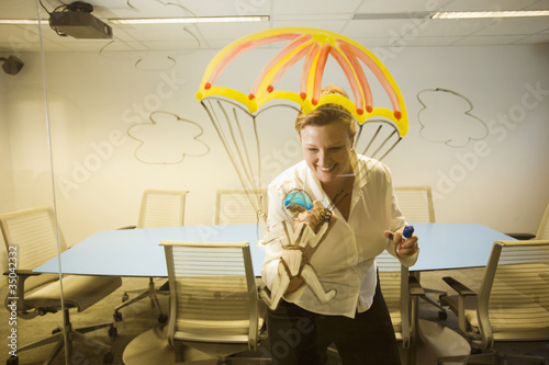 Caucasian businesswoman drawing a golden parachute on conference room wall