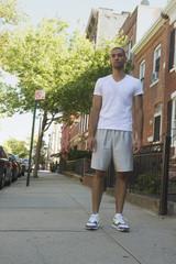 Mixed race man standing on urban sidewalk
