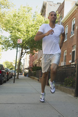 Mixed race man running on urban sidewalk