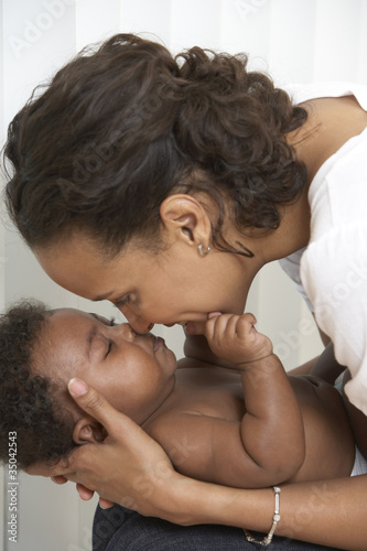 African American mother caressing baby