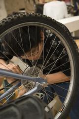 Hispanic boy repairing bicycle