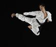 Asian male karate black belt kicking in air