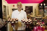 African American small business owner with cupcakes in bakery shop