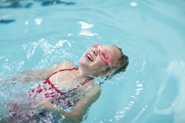 Caucasian girl swimming in swimming pool