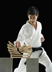 Asian male karate black belt breaking wooden planks