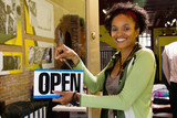 African American woman hanging open sign on door