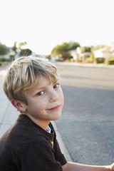 Caucasian boy sitting on curb
