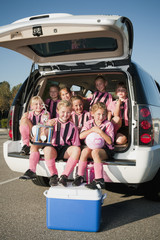 Girl soccer players sitting in back of car with trophy