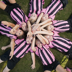 Girl soccer players laying in circle with arms raised