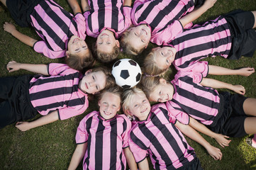 Girl soccer players laying in circle