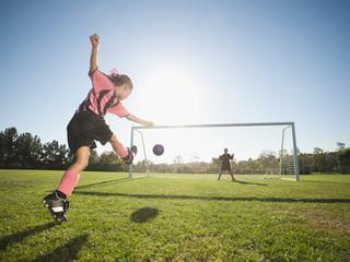Girl soccer player kicking soccer ball at net