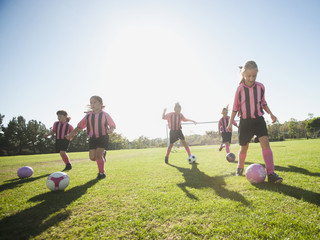 Girl soccer players practicing with soccer balls